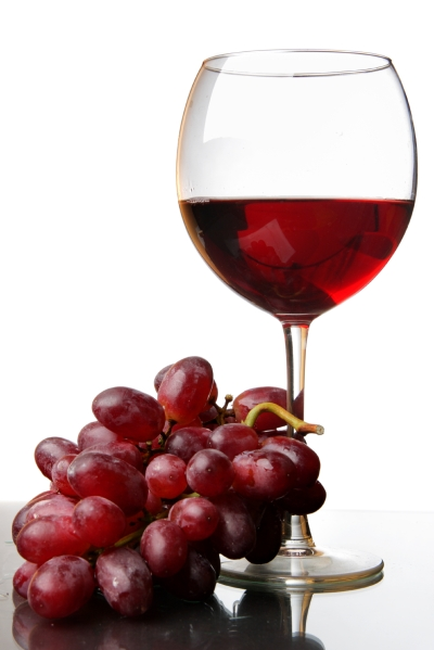 Glass of red wine and grape isolated over white background