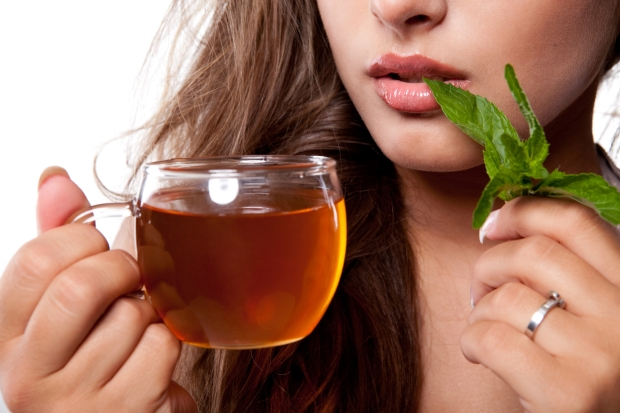 Woman with cup of fresh tasty mint tea
